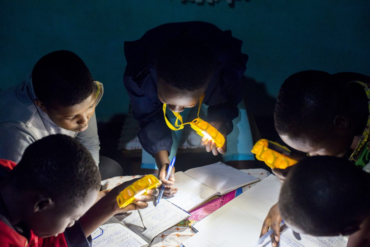 Children in Rwanda studying with Little Sun Original solar lamps. For every pair of sunglasses bought, #TOGETHERBAND will donate a solar lamp to children in Sub-Saharan Africa.